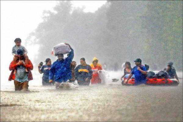 休士頓大都會區的哈里斯郡居民,廿八日成群涉水而過。(路透)
