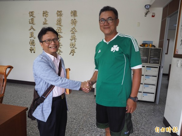 沈明正(左)握著王秋陽(右)的手一再稱謝,感謝他的拾金不昧。(記者陳鳳麗攝)