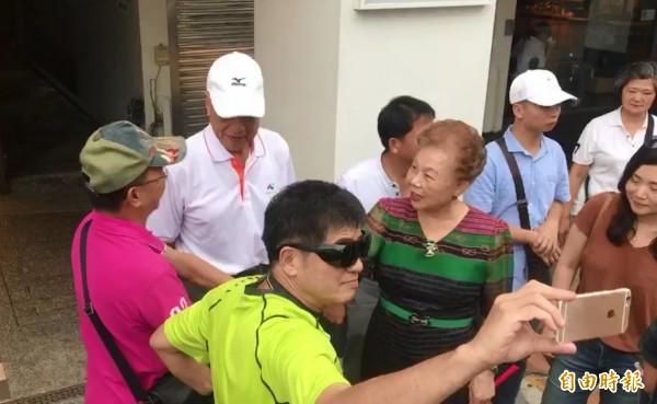 「柯爸」柯承發(左白帽者)和「柯媽」何瑞英(中綠衣者)受到民眾歡迎。(記者王煒博攝)