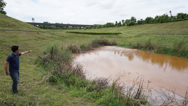 高市議員邱俊憲勘查疑遭污染河段,鄰近的滯洪池並未受影響。(邱俊憲提供