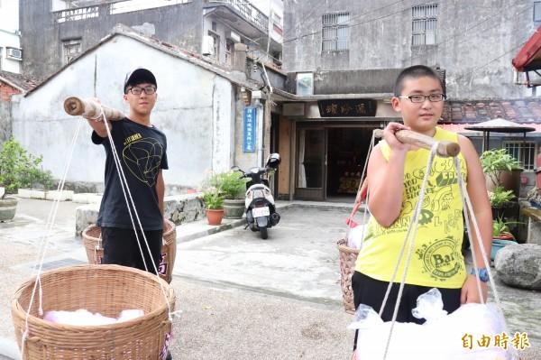 民間組織挑著擔子向民眾收孤飯的景象,近年在頭城街頭重現。(記者林敬倫攝)