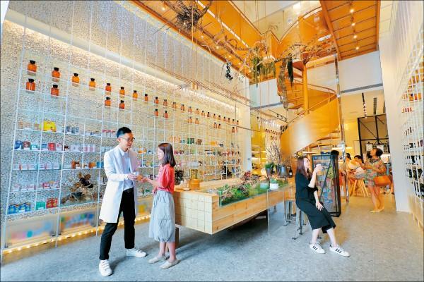 空間中央是以木質吧檯搭配古銅色迴旋梯金屬元素,模擬人類原始製藥情境,呈現綠色自然實驗風格。(記者李惠洲/攝影)