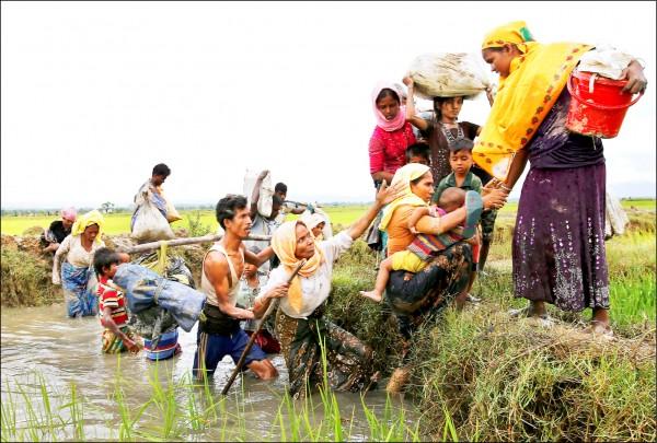 一群羅興亞難民一日越過孟緬邊界附近的一條水道。(路透)