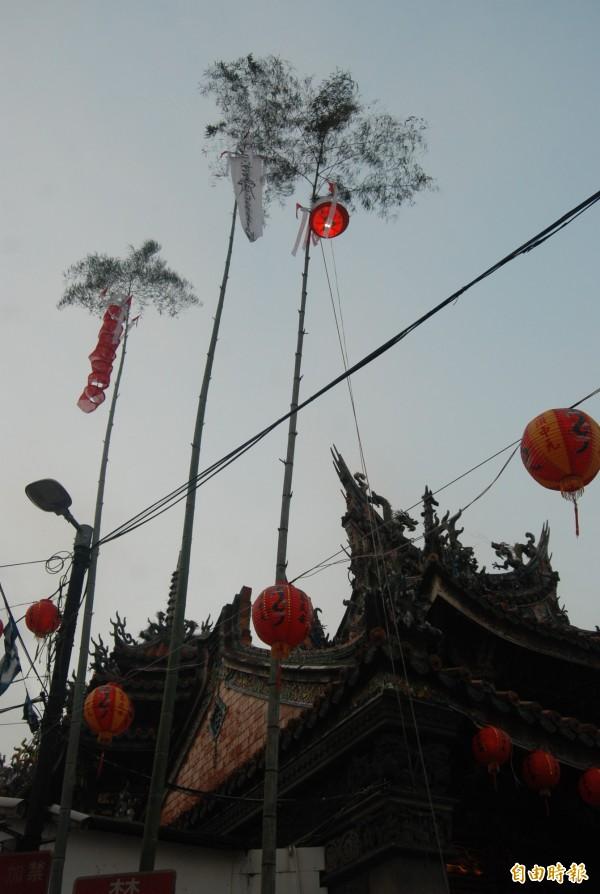 今年三峽祖師廟的燈篙高達5層樓,3根竹竿頂端掛著白布條及燈籠,底部則擺起香案。(記者張安蕎攝)