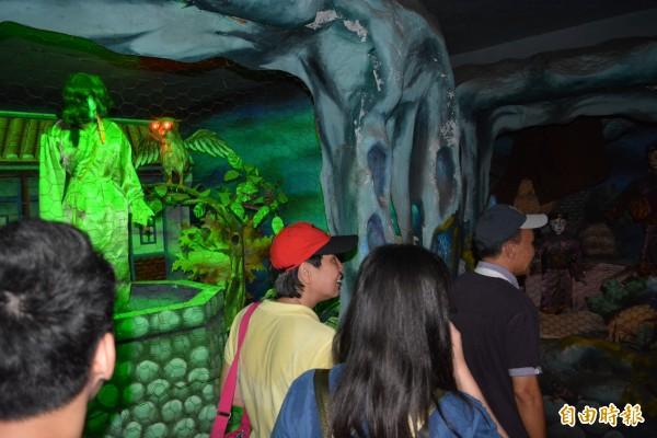 新加坡遊客在南天宮「魔界怪譚」試膽,被昏暗的聲光效果與恐怖人偶給嚇壞。(記者湯世名攝)