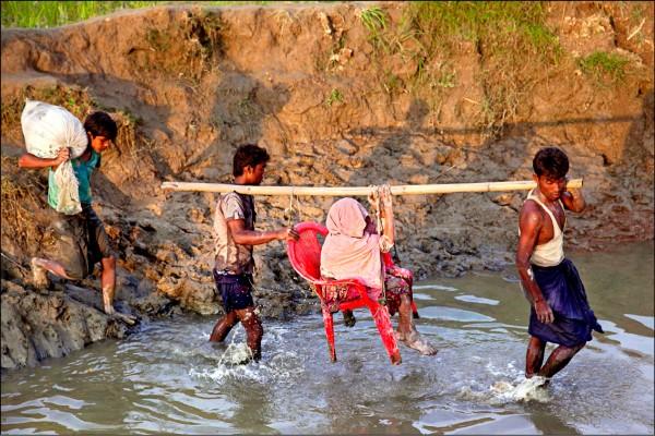 兩名羅興亞年輕人四日在緬甸、孟加拉邊境幫助一名老婦人渡河逃難。(歐新社)
