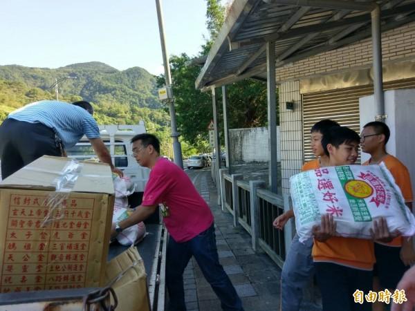 永和店仔街福德宮捐贈千斤白米,坪林國中學生開心協助卸貨。(記者翁聿煌攝)