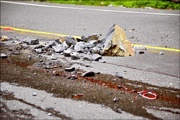 約至200公尺高山壁掉落的石塊,因重力加速度,還將路面砸穿一個大洞。(記者王峻祺翻攝)