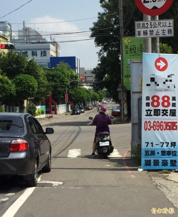 警方表示,如圖繫掛在路口的大型違規廣告看板,因為妨害行車視線,造成機車騎士等用路人會不自覺地越過停等區等候紅燈。(記者黃美珠攝)