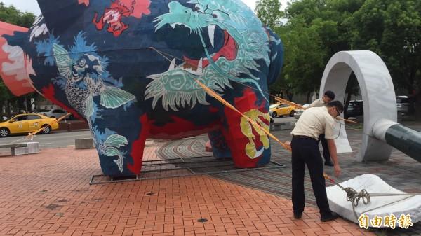 新竹縣政府文化局派員替創意彩繪神豬加強固定,以免颱風季被風「拐跑」。(記者黃美珠攝)