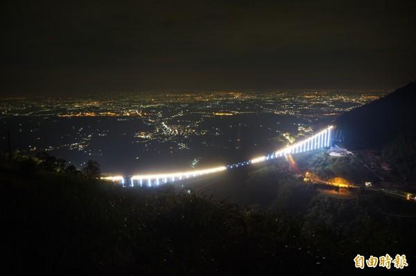 太平雲梯的橋體裝置近千個LED七彩燈條,民眾看見嘉縣山區的雲梯散發出如「微笑曲線」璀璨景致,認為是新地標,卻有民眾認為造成光害,影響生態環境,圖為7月27日試燈畫面。(記者曾迺強攝)