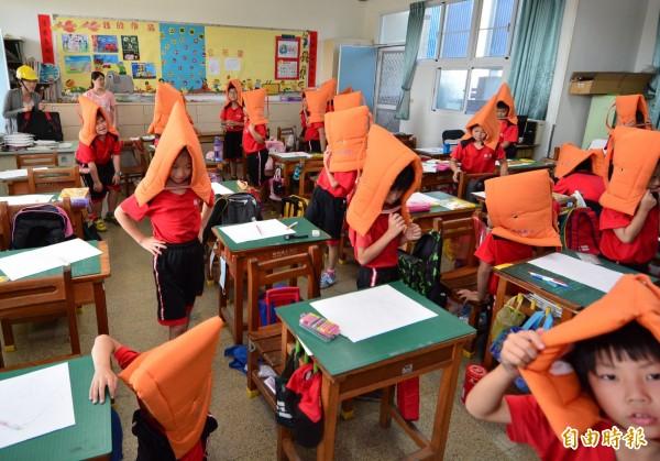 小朋友戴上頭套跟著老師離開教室。(記者張聰秋攝)