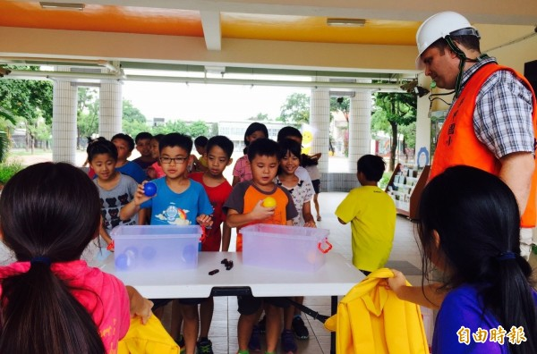 外籍教師戴安全帽避難裝備和學童玩互動遊戲。(記者楊金城攝)