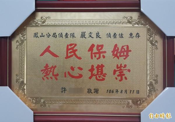許女打造一面獎牌「人民保母熱心堪崇」送給嚴員,感謝還她清白。(記者陳文嬋攝)