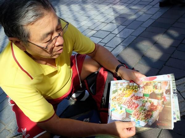 日本人中山泰浩今年74歲,非常喜歡台灣,過去5年來台灣21次,他秀出之前拍攝的台灣水果攤照片,說台灣水果真便宜。(中央社)