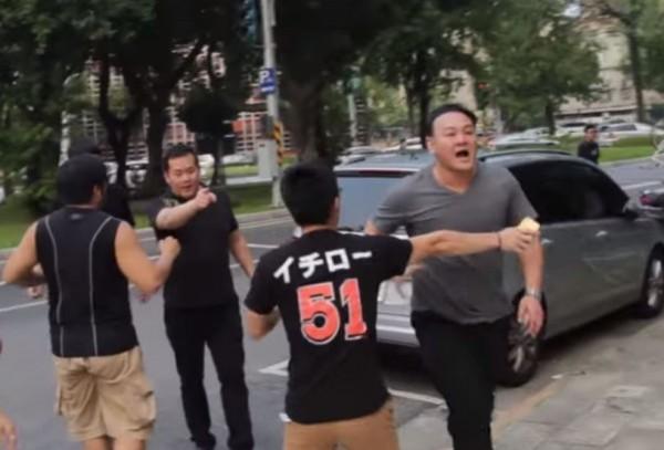 影片中帶頭打人的灰衣男子(圖右),疑為白狼張安樂次子張瑋。(翻攝自youtube)
