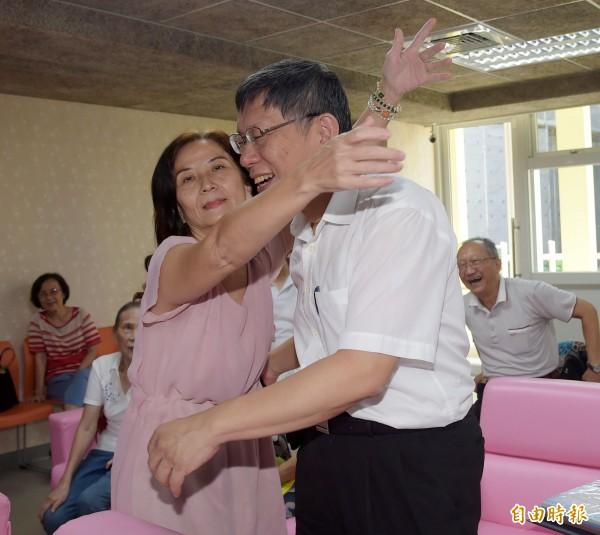 台北市長柯文哲26日走訪中正老人服務暨日間照顧中心,與長者一起玩遊戲、做運動,一旁的爺爺在投籃後對柯文哲比出讚。(記者黃耀徵攝)
