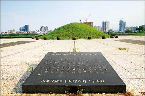 台北馬場町紀念公園中央有一座紀念土丘,前方的黑色紀念碑寫了紀念緣由。(記者臺大翔/攝影)