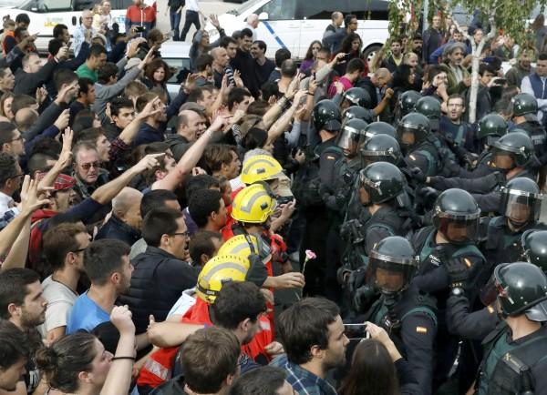 西班牙加泰隆尼亞自治區1日展開獨立公投,大批鎮暴警察前往投票所阻撓民眾投票。(歐新社)
