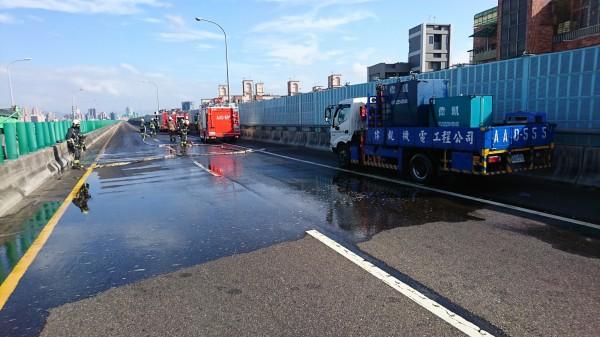 警消封鎖漏油路段排除路面油漬。(記者王宣晴翻攝)