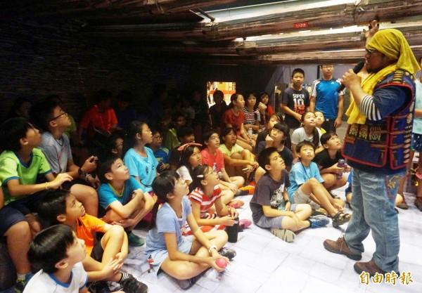 杜寒菘在石板屋內講故事,跟小朋友分享有趣故事。(記者張忠義攝)
