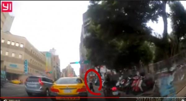 一名行人(紅圈處)就這麼衝出來,害得畫面中的機車騎士迎頭撞上。(圖擷取youtube)