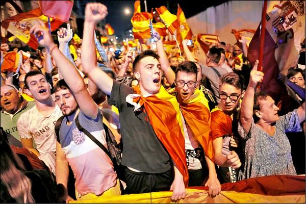 反對加泰隆尼亞脫離西班牙獨立的示威者,五日在加泰隆尼亞首府巴塞隆納市郊聚集,呼喊反獨立口號與揮舞西班牙旗幟。(美聯社)