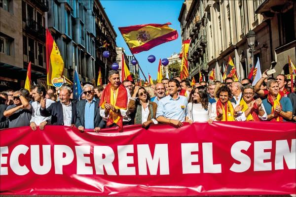 西班牙加泰隆尼亞自治區八日發起「反對獨立」遊行,執政黨「人民黨」的加泰隆尼亞地區領袖阿爾比奧(第一排左五),與曾獲諾貝爾文學獎的作家尤薩(第一排左四),一同站在寫著「夠了!恢復理智」的示威布條後,帶領數十萬人表達希望西班牙團結的心聲。(彭博)