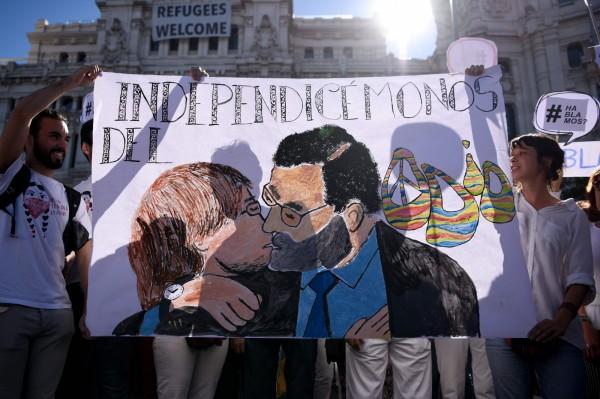 加泰隆尼亞爭取獨立、脫離西班牙。西班牙人在馬德里高舉西班牙總理拉霍伊和加泰隆尼亞自治區主席普伊格蒙特親吻的海報。(法新社)