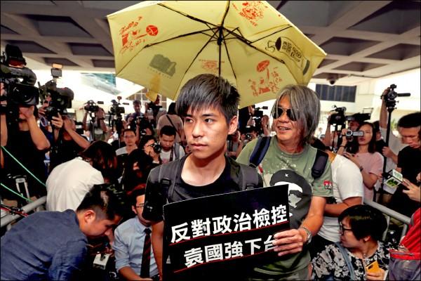 香港學聯前副秘書長岑敖暉十三日前往高等法院聽判,手持寫有「反對政治檢控,袁國強下台」的標語。袁國強是香港特區政府律政司司長。(路透)