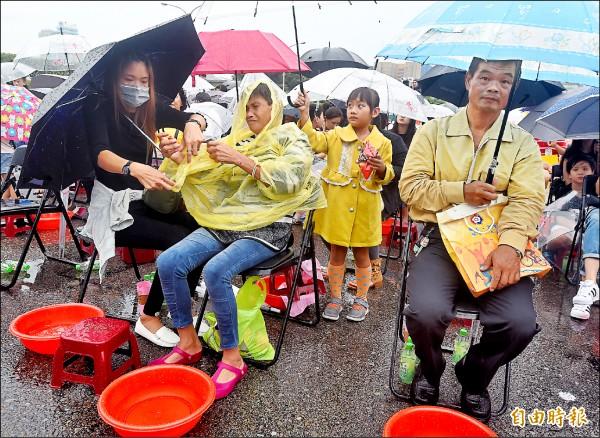 主辦單位缺乏規劃,民眾冒雨枯等兩小時才開始洗腳活動,完全失去活動宣導的意義。(記者廖振輝攝)