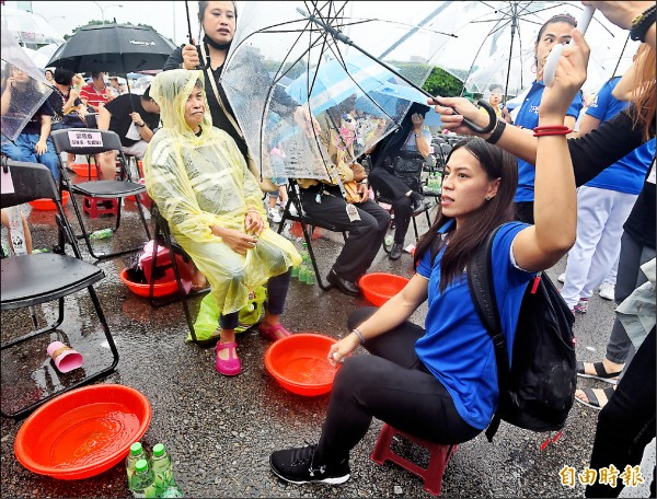 世大運舉重金牌選手郭婞淳(右一)等人,也冒雨枯等兩小時才開始幫長輩洗腳。(記者廖振輝攝)