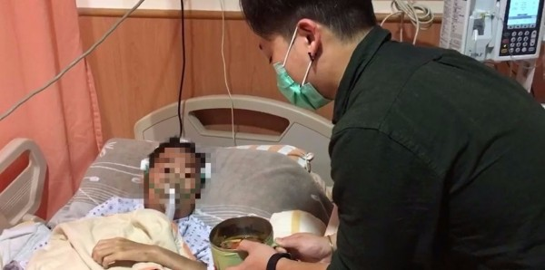 高雄花葵壽喜燒游老闆(右)將煮好的壽喜燒拿給癌末患者(左),幫他圓夢。(家屬提供)
