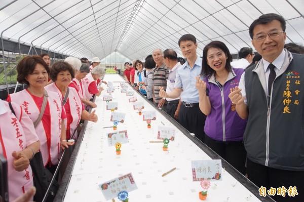 台中市社會局副局長陳仲良等在水耕蔬菜區種下芥蘭菜苗,並寫上名字,等待日後收成。(記者歐素美攝)