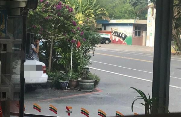 游姓車手躲在車子旁鬼鬼祟祟,一舉一動都被埋伏員警拍照。(記者楊金城翻攝)