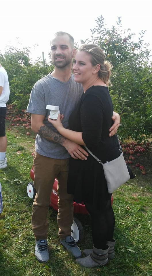 美國一名女子在男友下跪求婚時以為又是開玩笑怒擲蘋果爆對方的頭,後來發現這次是真的開心到不行。(圖擷自臉書)