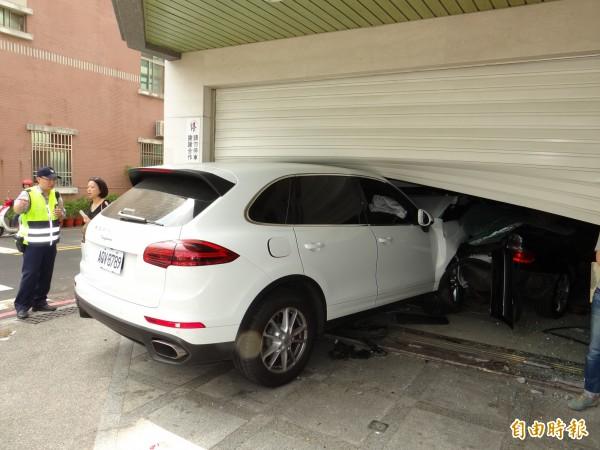 車速很快的保時捷休旅車把停在民宅騎樓的賓士車撞進屋內,警方到場調查。(記者王俊忠攝)