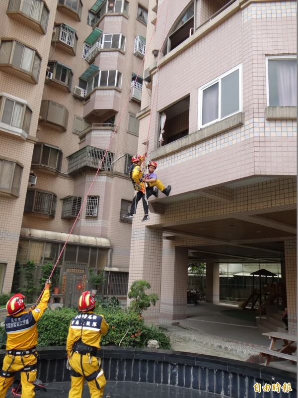 虎尾寮緊急救援隊員以繩索垂吊方式從大樓救下受困居民。(記者王俊忠攝)