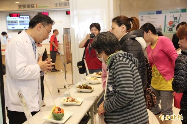 民眾好奇的觀看適合癌友飲食的料理。(記者張勳騰攝)