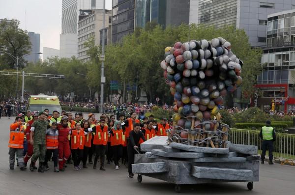 在地震廢墟中找尋倖存者的救難人員參加「死亡遊行」。(美聯社)