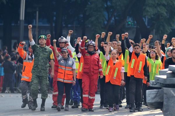 參加遊行的救難人員高舉著拳頭,這是救難人員要求沉默的信號,以聽清楚是否有倖存者被困在廢墟中。(法新社)