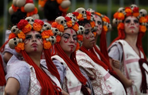 臉上畫著骷髏妝、頭戴骷髏裝飾的數百名表演者上街遊行,以此向9月2次強震數百罹難者和救難人員致意。(美聯社)