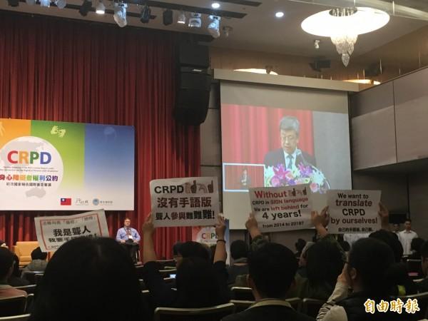 身心障礙者權利公約(CRPD)初次國家報告國際審查會議開幕,場中出現民眾舉牌抗議。(記者林彥彤攝)