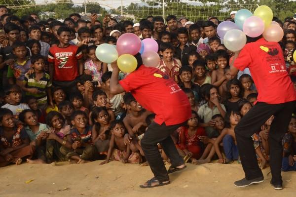 孟加拉的庫圖巴朗(Kutupalong)難民營中,拿著氣球的馬戲團團員們逗笑一張又一張羅興亞難民小小的笑臉,讓這裡充滿奇蹟般的笑聲。(法新社)