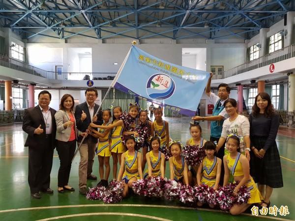 新進國小競技啦啦隊將於11月10日前往日本參加2017年啦啦隊世界錦標賽,今由即將接任農委會副主委的家長會長李退之授旗。(記者王涵平攝)