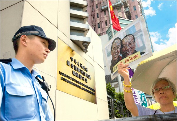 中聯辦十一月擬邀集香港中學校長及教師,討論初中的中國歷史課程。相關消息引發輿論譁然,港媒指出,中國對香港年輕世代的「意識形態控制」已化為實際行動。圖為香港民眾七月間在中聯辦外高舉已故諾貝爾和平獎得主劉曉波與其妻劉霞的合照抗議。(歐新社檔案照)