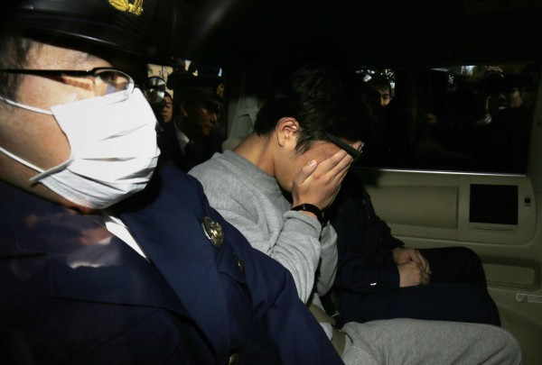 白石隆浩(摀臉者)表示,曾要求第一名受害者將50萬日圓匯入自己的銀行帳戶,藉此租下犯案公寓。(法新社)