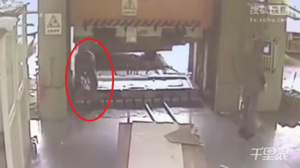 中國一名在工廠上班的工人,沒被同事察覺他身在大型液壓機底下,同事啟動液壓機導致他慘死。(圖擷取自LiveLeak)