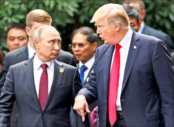 美國總統川普(右)與俄國總統普廷11日在進行APEC峰會大合照時,又被拍到邊走邊交談。(法新社)