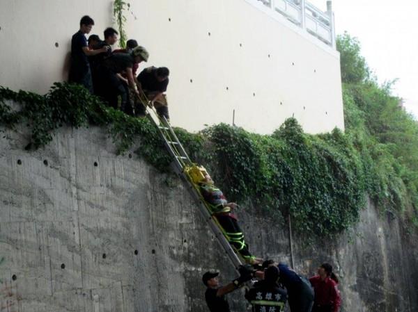 呂姓女子坐在半山壁上,警、消費了一番功夫才把呂女從山壁上救下。(記者黃佳琳翻攝)